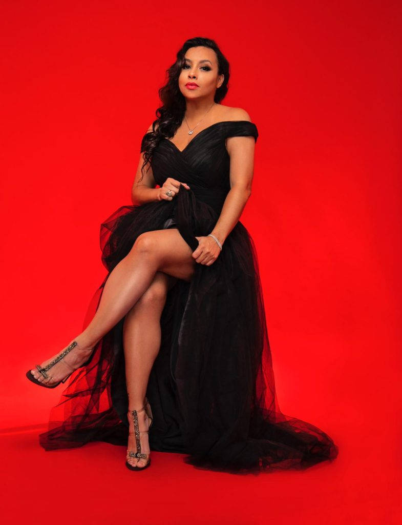 Super bowl Latina designer Lila Nikole wearing a fluffy black dress